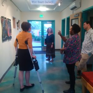 Heather Leigh, Brittnee Page, Marc Paley, and guest examine the gallery exhibition.
